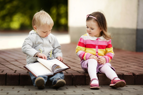 this little boy is showing the importance of reading at an early age, as he is able to now confidently read to his friends