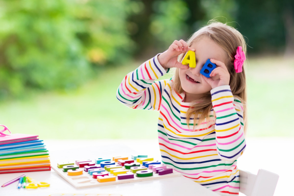 6 year old girl playing reading games with alphabet blocks