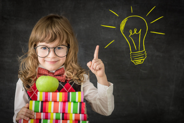 A little girl showing pointing to a light bulb and showing that becoming literate is important