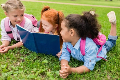 A group of 1st graders reading together outside