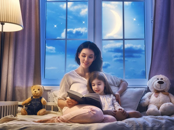 A mother reading with her child in bed to help her overcome her struggles